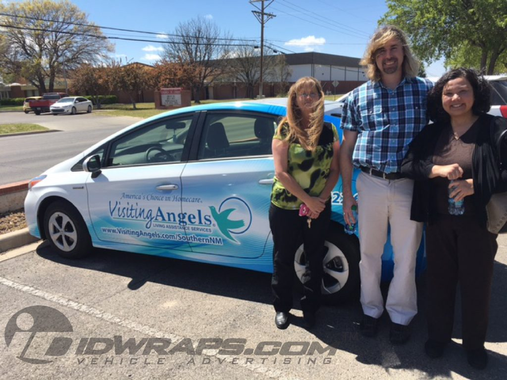 Prius graphic wrap pictured with proud owners and staff.